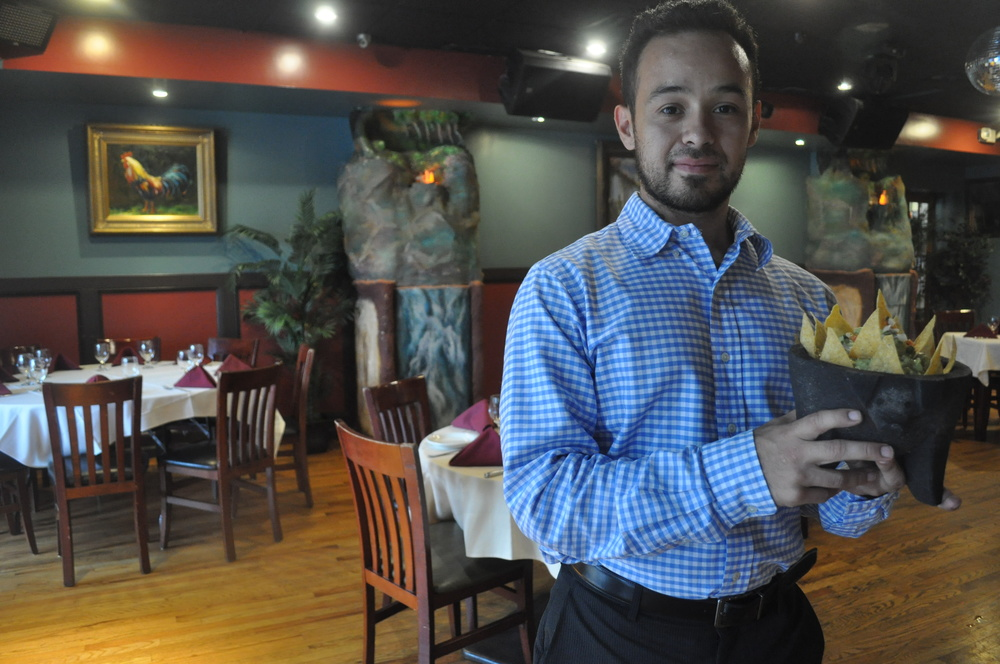 Jose Reyes Jr. showcases Anaconda Latin Bistro's guacamole – served in a stone, pig-shaped dish – in the redesigned dining room Saturday.