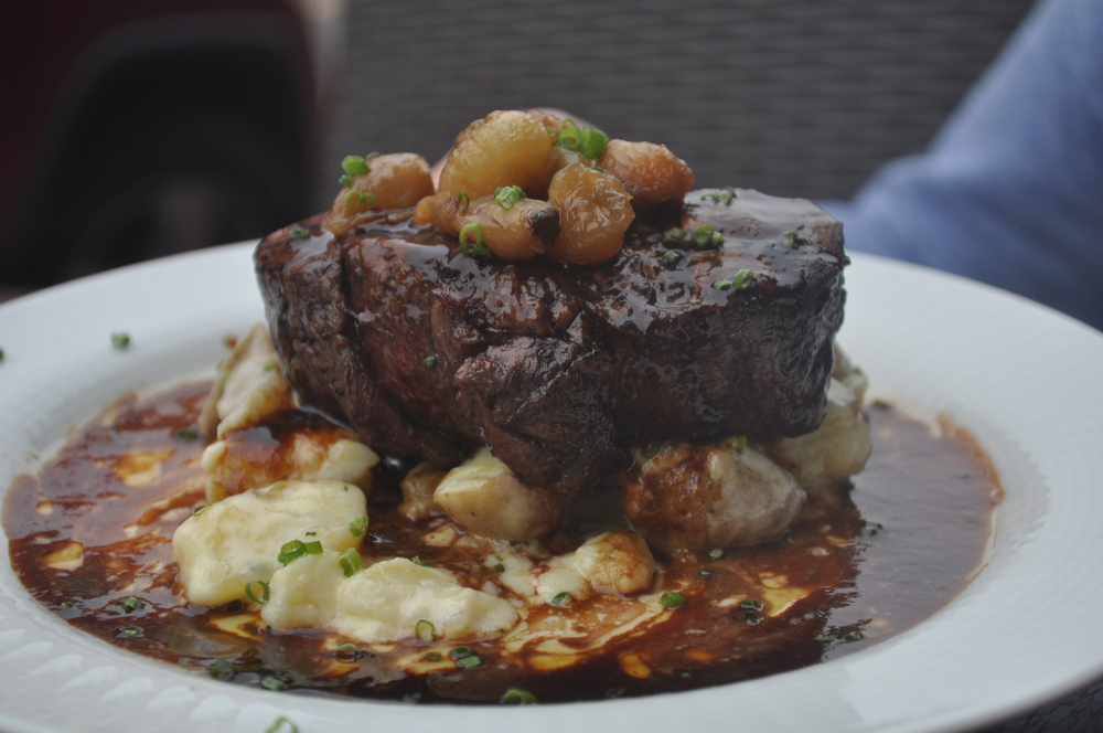 The 8oz. filet mignon shines atop garlicky smashed potatoes, caramelized cipollini onions and a rich burgundy sauce.