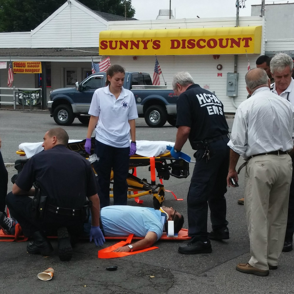 Huntington Community First Aid Squad volunteers treat an injured man at the scene of a hit-and-run incident in Huntington Station Thursday morning.