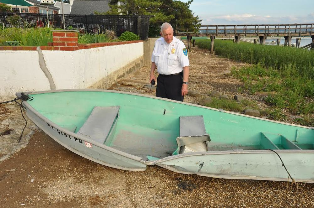 Asharoken Police Officer-in-Charge Ray Mahdesian inspects inspecting damage to a rowboat that was hit by a 22-foot vessel Friday afternoon. Photo by Steve Silverman