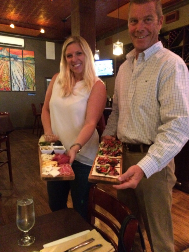 The Wine Cellar owners Lindsay Ostrander and Michael O'Brien display a cheese and meat board and an artisan flatbread board.