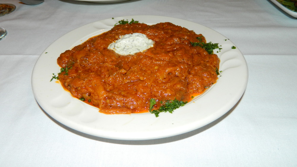 The kashk bademjan consists of cooked eggplant in tomato sauce topped with yogurt.