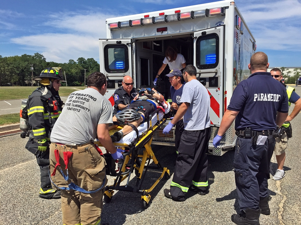 A 48-year-old Dix Hills bicyclist, injured in a fall Saturday morning, is transferred to a Dix Hills Rescue Squad ambulance by first responders. Photo/Dix Hills Fire Department