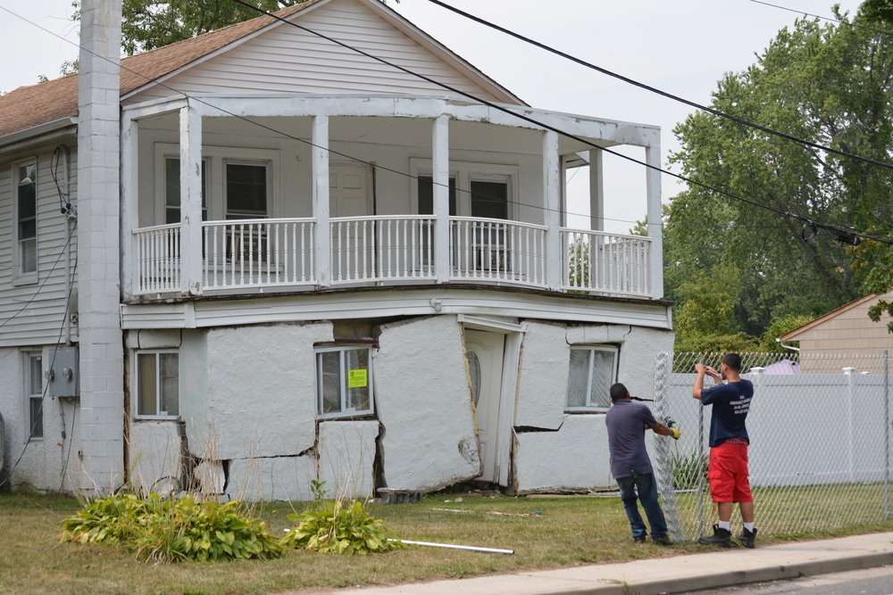 Workers put up a fence around a West Babylon home that was struck by a vehicle Sunday night in a fatal accident. Town of Babylon officials have condemned the house due to extensive damage.