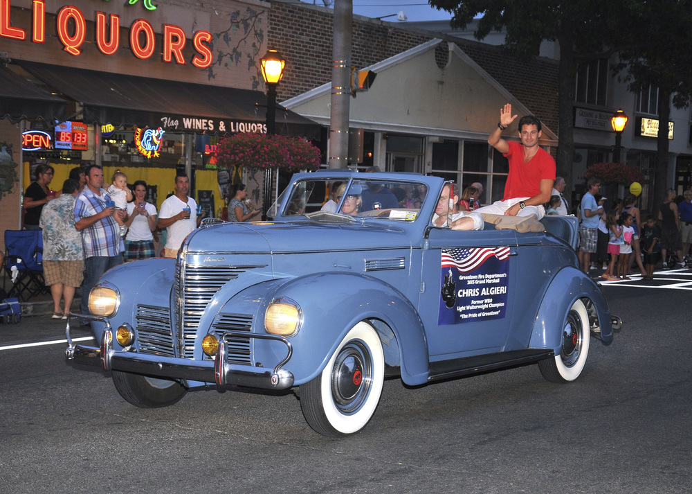 Professional boxer and Greenlawn native Chris Algieri visited his old stomping grounds last Thursday, when he was honored as a grand marshal at the 112th annual Greenlawn Firemen's Fair parade. Above, Algieri waves as he rides up Broadway in a vintage '39 Plymouth. Photo by Steve Silverman