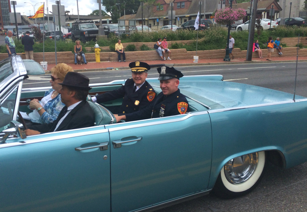 Huntington Awareness Day parade grand marshal Ed Brady, the retired commanding officer of the Suffolk County police Second Precinct, rides in style with honoree, Suffolk County Police Officer Mark Collins.