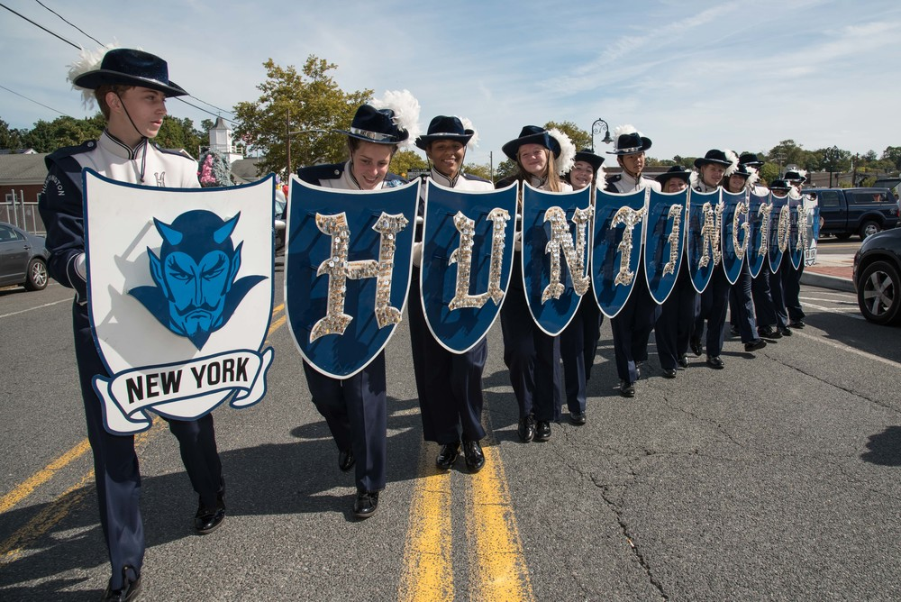 The Huntington marching band displays their shields in a showing of school pride during their parade march through the town streets on the day of the Huntington Homecoming event held on Sept. 26. (Photo / Jim Hoop)
