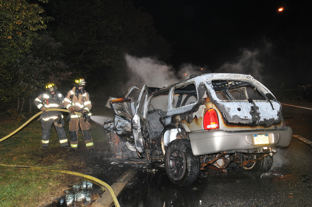 Dix Hills firefighters extinguish a blazing SUV involved in wrong-way crash  that killed two people on the Northern State Parkway in Dix Hills early Tuesday morning. (Photo by Steve Silverman)