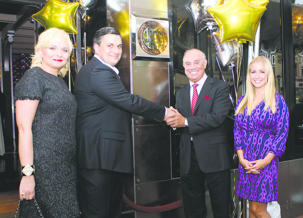IMC Restaurant owners Oksana and Igor Chukhriy receive congratulations from American Academy of Hospitality Sciences Chairman Joseph Cinque and trustee Kateryna Bliss beneath a plaque proclaiming the restaurant's Five-Star Diamond designation.