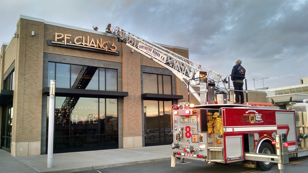 Firefighters from the Huntington Manor Fire Department investigate the roof of the P.F. Chang's restaurant at the Walt Whitman Shops to determine the source of smoke that filled the restaurant Sunday evening. (PHoto / Steve Silverman)