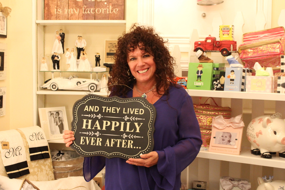 Eileen Pinchuck, owner of Jewelry Collection, is loving life as she stands in her bridal and baby section in her shop on Main Street in Northport.