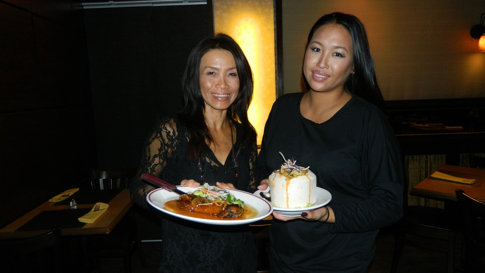 Owner Tiki Choladda and daughter, Pathra, presenting shrimp in young coconut and duck entrees.