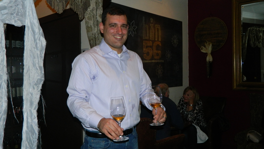Owner Daniel Pedisich presents Kabaj Rebula wine to pair with a grilled bratwurst entrée.