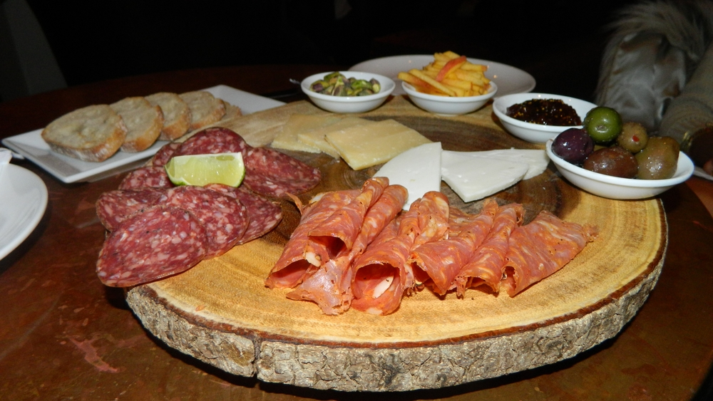 A goat gouda, zigljen cheese, beef salami, pork sausage and olives platter.
