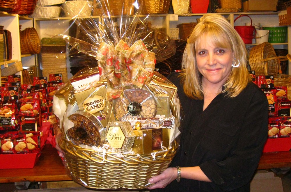 Lisa Mettrock, owner of A Tisket, A Tasket Anything In A Basket, working from her private workroom, arranging baskets filled with mixed nuts, crackers, chocolates and more.