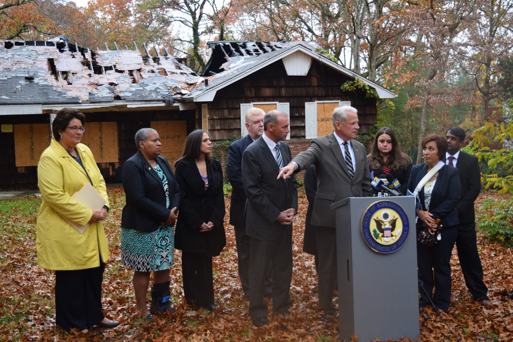 U.S. Rep. Steve Israel (D-Huntington), center, is joined Nov. 10 by several local politicians and members of the community after announcing a bill that seeks to turn blighted homes – such as the Dix Hills home pictured – into housing for homeless veterans.