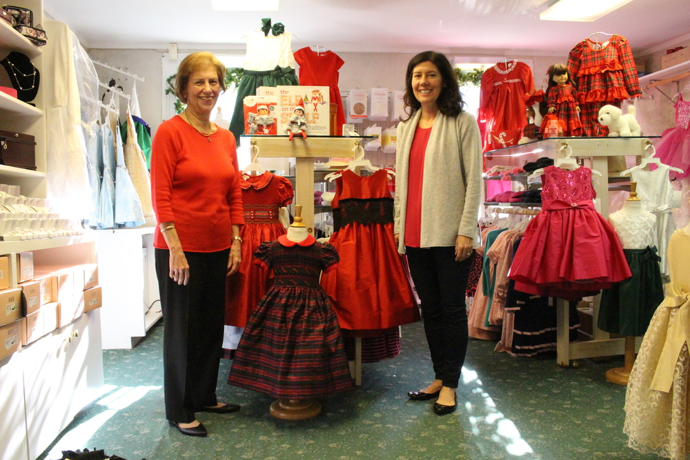 Pat Ramsay, founder of Pashley's Children's Boutique, and daughter Debbie Schiper, co-owner, standing by girls Christmas dresses.