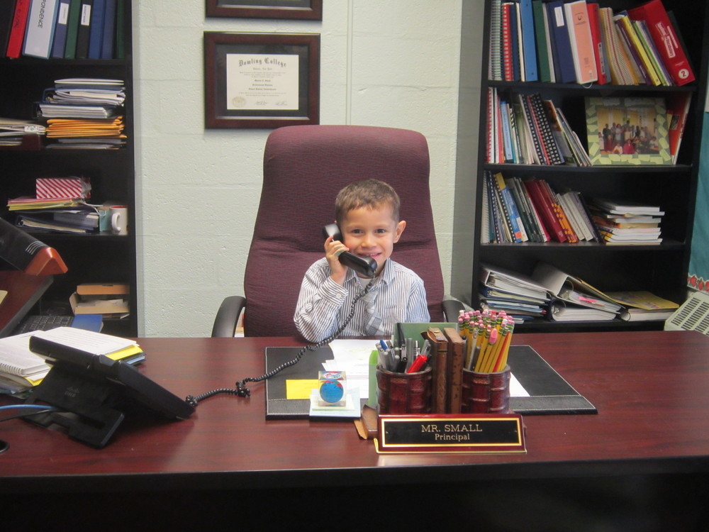 Huntington   kindergartener Kaiden Maldonado serves as principal of Flower Hill Primary School for a day. Inset, Kaiden stands with Flower Hill Principal Marlon Small in the school's main office.