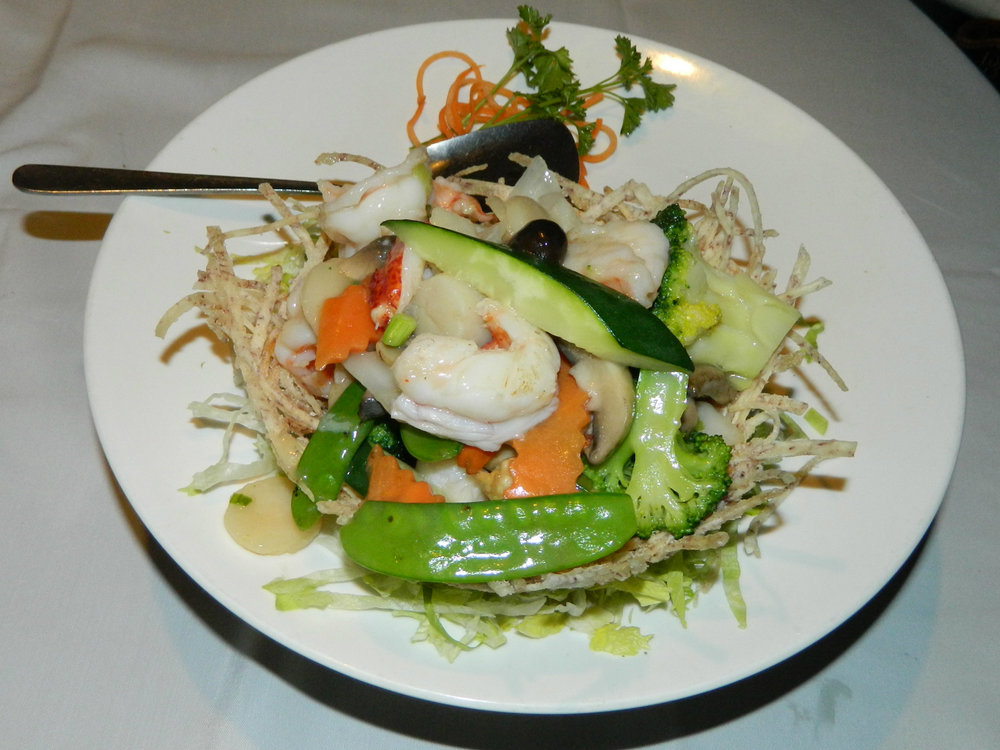 The Seafood Delight entree is made with lobster, prawns and scallops. It is sauteed with vegetables and presented in a bird's nest basket made from taro root.