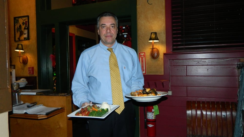 Owner Fernando Murta presents linguine pescatore and pollo alla Nino.