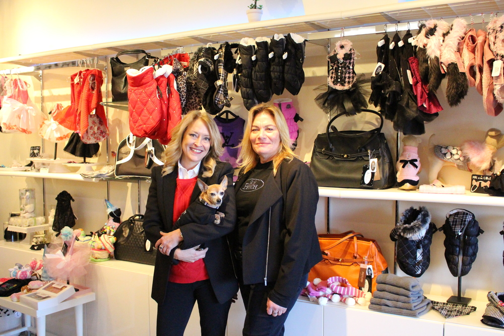 """Owners of Fetch Karen Durka, holding """"chief barking officer"""" CoCo, and Susan Levine sell doggie apparel such as vests, coats, sweaters and more."""