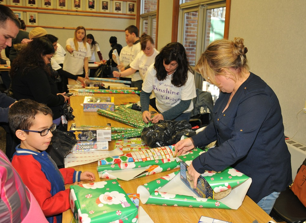 Volunteer personal shoppers and gift wrappers take to the toy store that was assembled at the Dix Hills firehouse last month as part of the ninth-annual Sunshine Toy Drive. Photo by Steve Silverman
