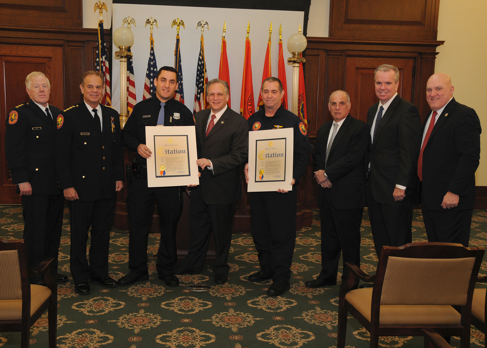 :     Left to right: Nassau Chief of Patrol Frank Kirby; Chief of Department Steve Skrynecki; Fourth Precinct Police Officer James Sarnataro Jr.; Nassau Executive Edward Mangano; Aviation Bureau Police Officer James Sarnataro; Deputy County Executive for Public Safety Chuck Ribando; Acting Police Commissioner Thomas Krumpter; and Nassau PBA President James Carver.  Photo by Nassau County