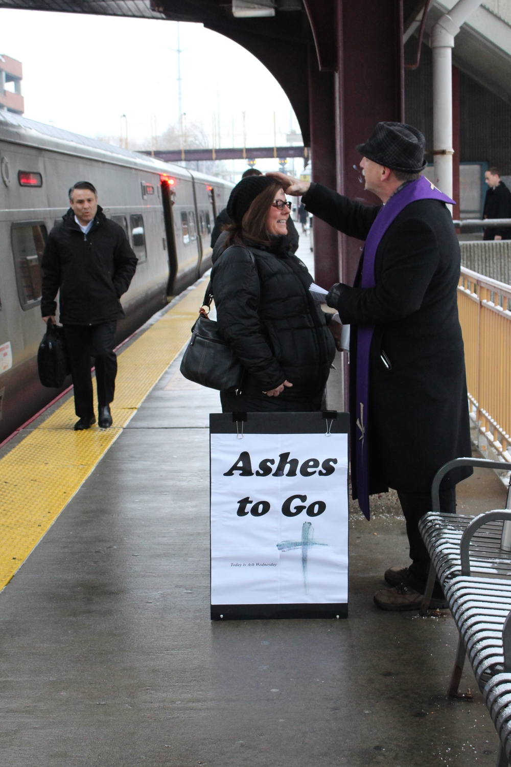 Camille Fiato of Huntington smiles as she stops to receive her ashes on Ash Wednesday from Rev. Joel Brandt before her morning commute to Manhattan.