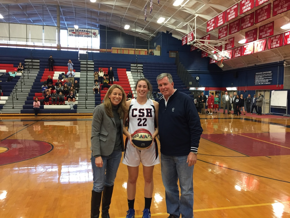 Cold Spring Harbor's Caroline Kiernan with parents Cheryl and Matt after scoring the 1,000 point in her four-year varsity career during a game against the East Rockaway Rocks on Tuesday. Photo by Michael Bongino