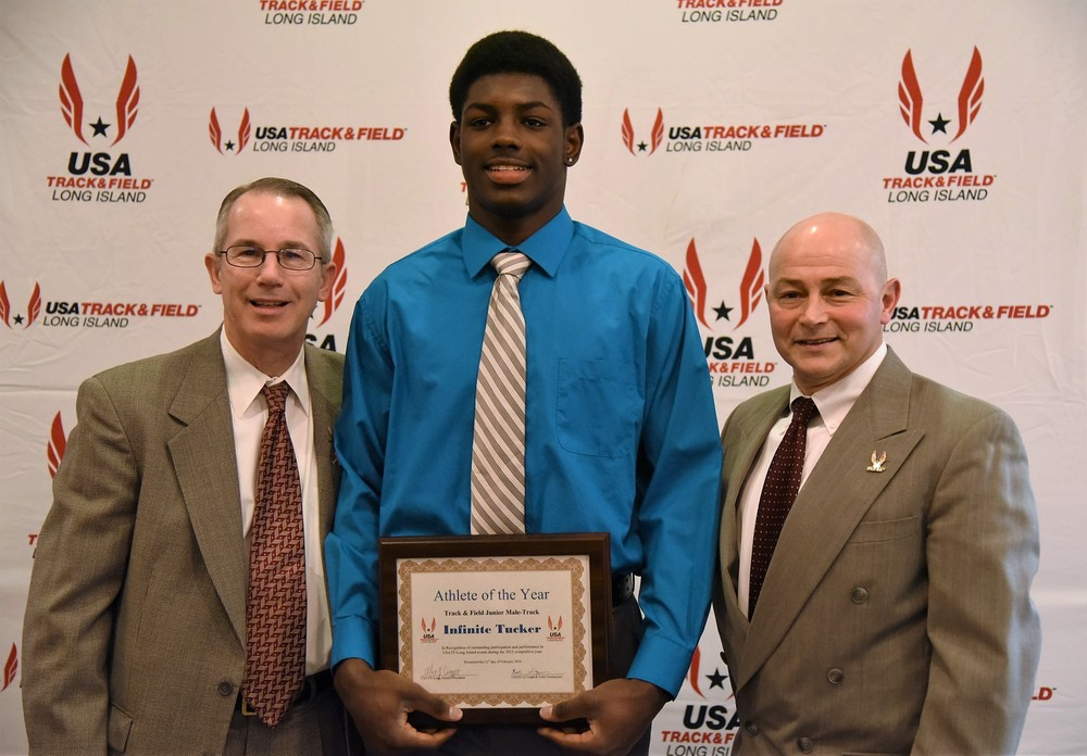 Blue Devils track star Infinite Tucker is flanked by officials from the Long Island Track and Field Association. Photo/Huntington Union Free School District