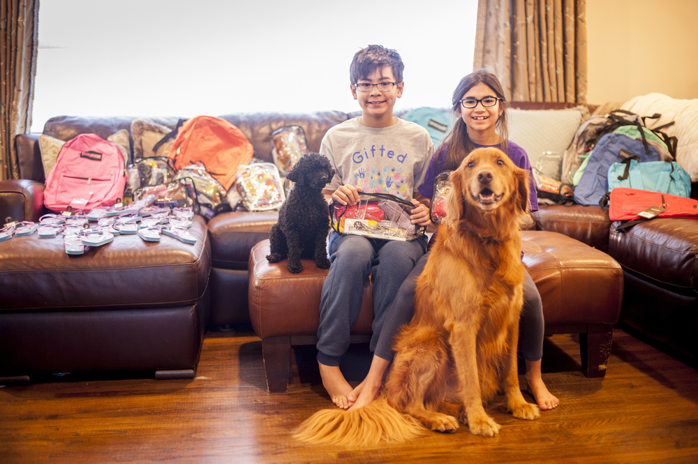 Brother and sister T.J. and Isabella Manfuso, of Northport, sit with their dogs Max and Lucy among the medical care packages and school supply backpacks they created and will donate to children in various Central American and South American countries.