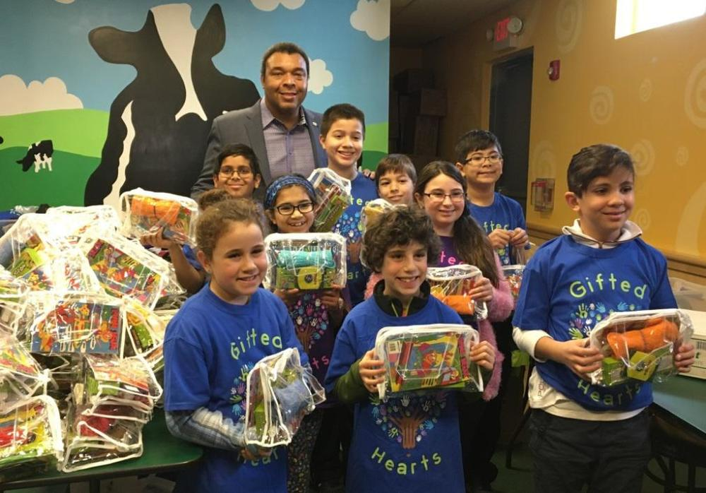 "Suffolk County Legislator William Spencer (D-Centerport) joins T.J. and Isabella Manfuso and their volunteer group as they host a ""packing party"" to package supplies for children in need beyond Long Island's borders."