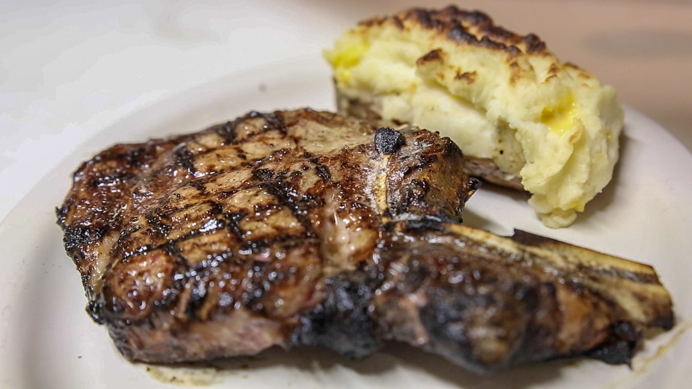 : The bone-in rib eye steak at The Clubhouse is served with a stuffed baked potato.