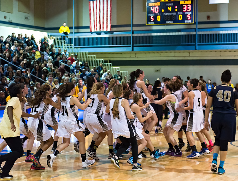 The Commack Cougars celebrate the team's second straight Long Island championship following a 40-33 win over Baldwin on Saturday at St. Joseph's College.