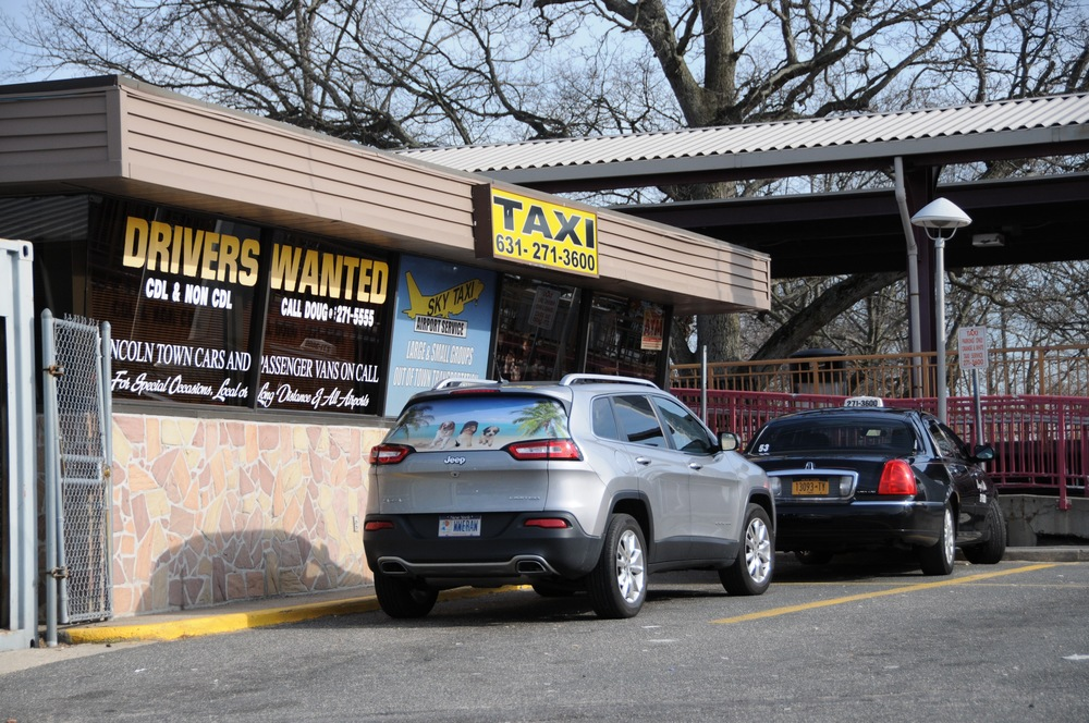 A total of 60 local taxi drivers, including drivers from Huntington Station-based taxi company Orange & White, above, wrote to the Huntington Town Board on March 7 imploring the board to enforce town code and prevent Uber drivers without appropriate licensing from servicing customers within town lines.