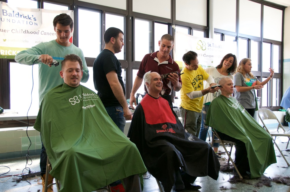 Walt Whitman High School Principal John Murphy and South Huntington Teachers Association President Dennis Callahan join, on Wednesday, the annual St. Baldrick's shavathon at Walt Whitman High School.