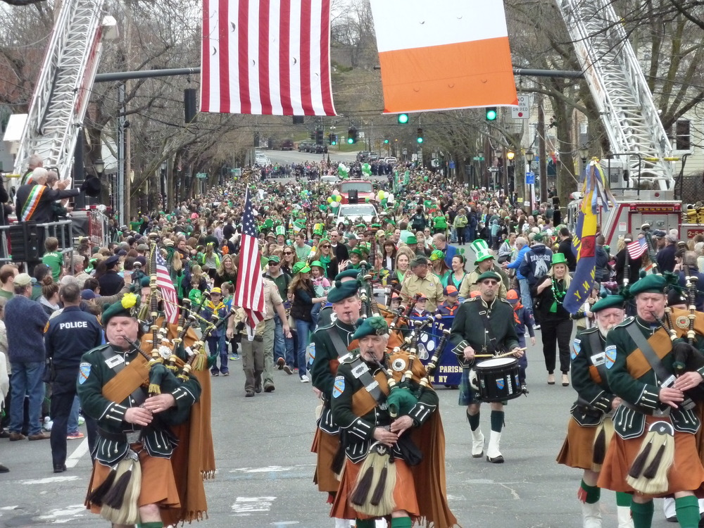 The County Armagh Pipe Band marches beneath American and Irish flags and approaches the reviewing stand near the Main Street and West Neck Road intersection.