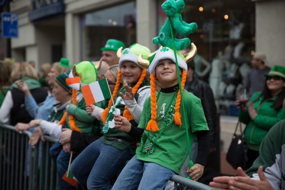 Onlookers, decked out in green and sporting St. Patrick's Day-themed attire, are wide-eyed and smiling during Sunday's parade.