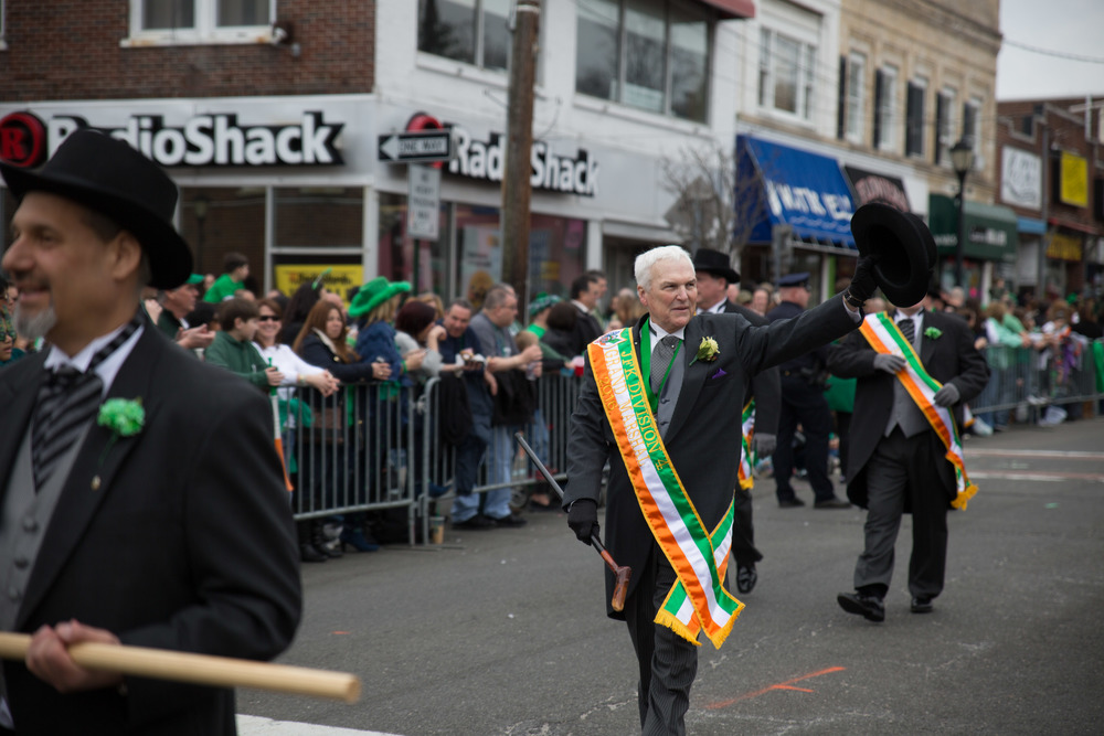 "Parade Grand Marshal John W. ""Jack"" Ryan greets paradegoers on Sunday. Ryan is the current Ancient Order of Hibernians Suffolk County board president, and chairman of charities and missions."