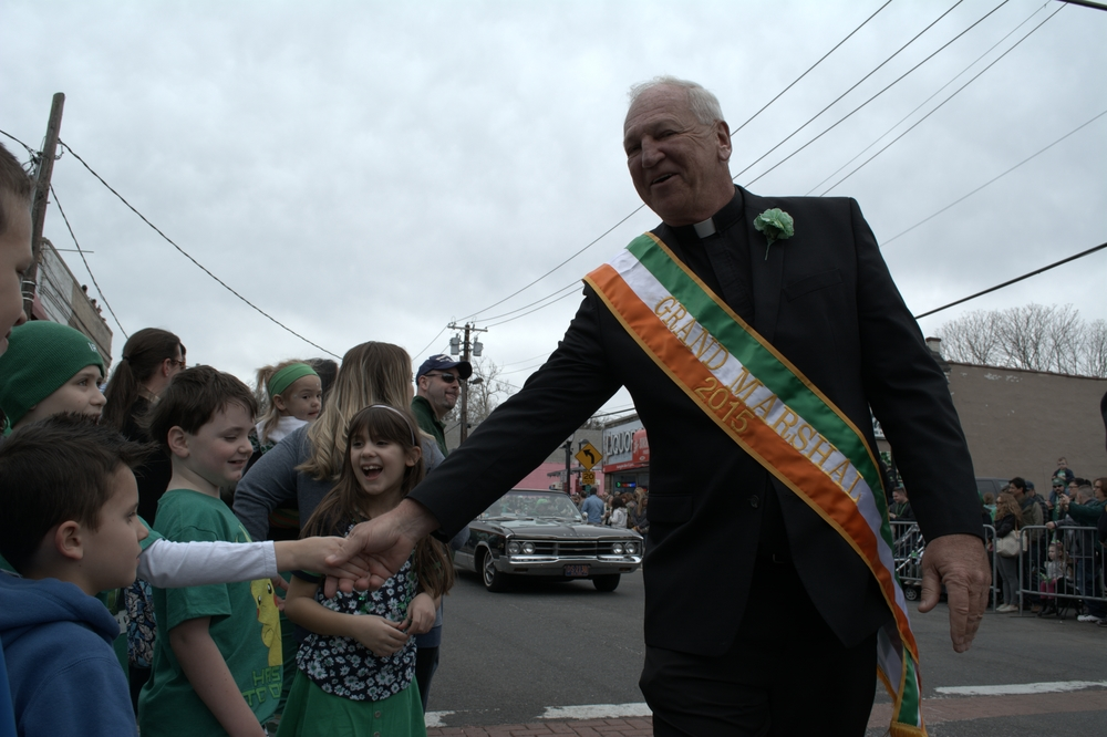 Grand marshal of last year's Huntington St. Patrick's Parade, Rev. Stephen Donnelly, makes his way up New York Avenue, greeting a few young onlookers along the way.
