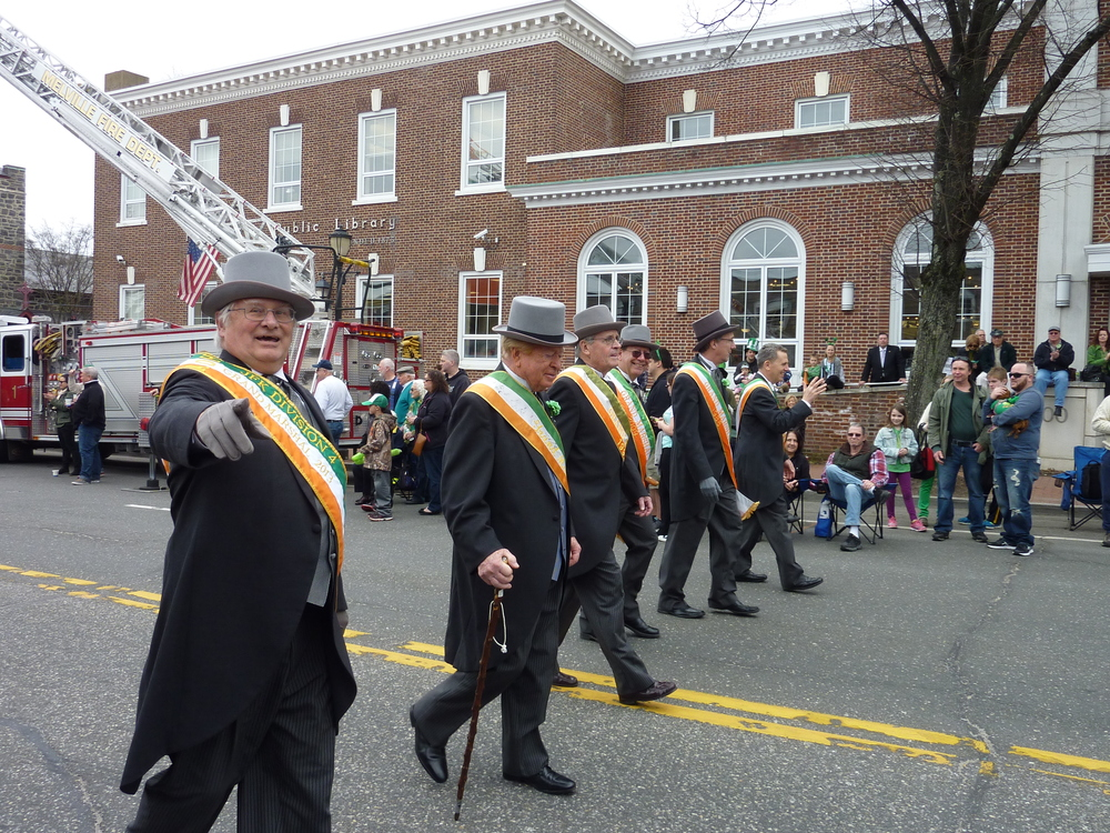 Past grand marshals of the annual Huntington St. Patrick's Parade pass by the Huntington Public Library.