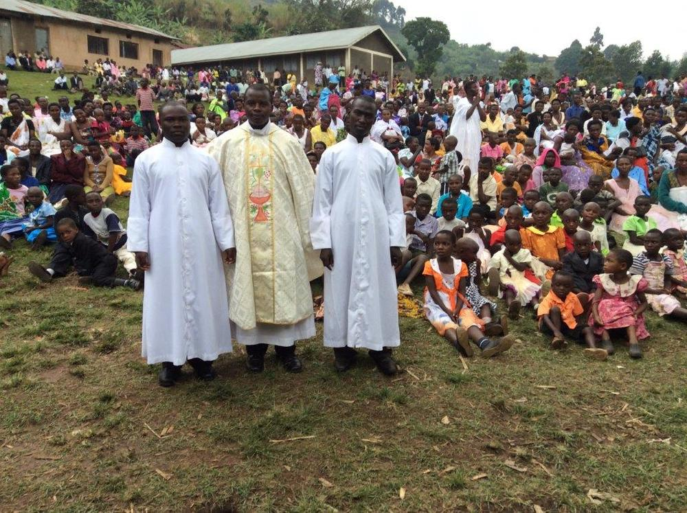 Father Vian Ntegerej'Imana, standing center, is the associate pastor at St. Anthony of Padua Church in East Northport. Students at the church are raising money toward construction of Father Ntegerej'Imana's home village in Kisoro, Uganda, which is pictured.