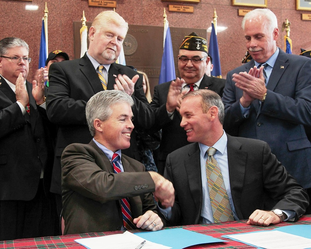 Suffolk Legislator Steve Stern, sitting right, and County Executive Steve Bellone, sitting left, are pictured in 2014 after Stern's Housing Our Homeless Heroes Act was signed into law. This week, Bellone endorsed Stern in his primary run for the Third Congressional District seat.