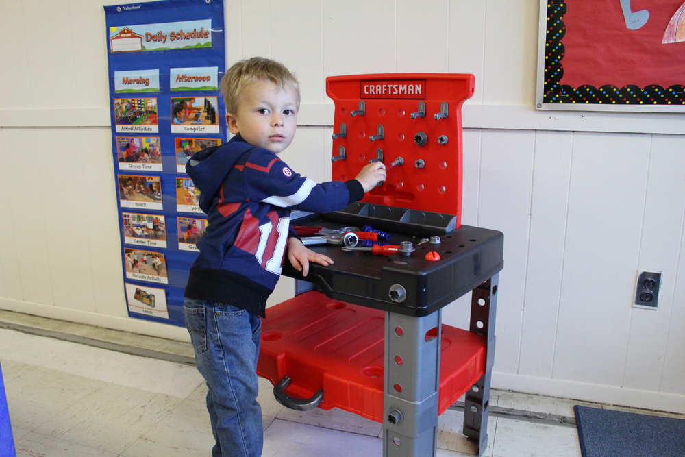 By playing with tools, Hunter Hogan, 3, Plainview, is practicing his fine motor skills at Alternatives For Children in Dix Hills. Hunter's mom, Vivienne Viera, is the curriculum coordinator for AFC.