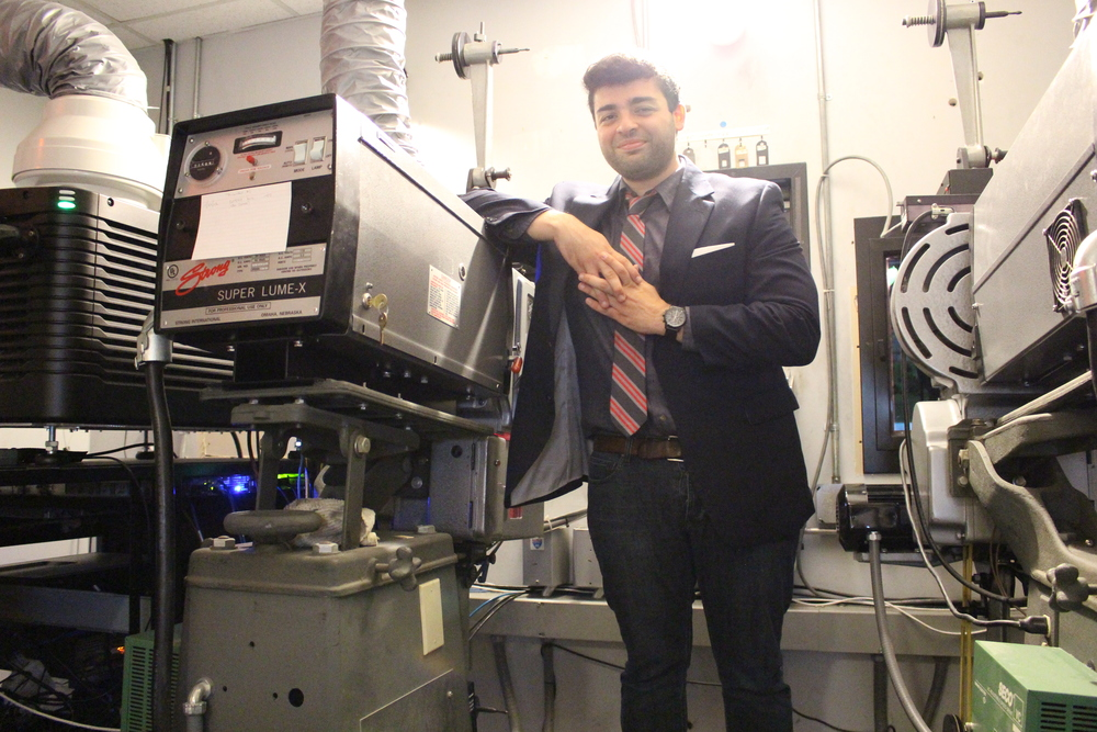 Raj Tawney of Commack, director of publicity and promotions at the Cinema Arts Centre, gets behind the scenes at the cinema, standing next to a film projector.