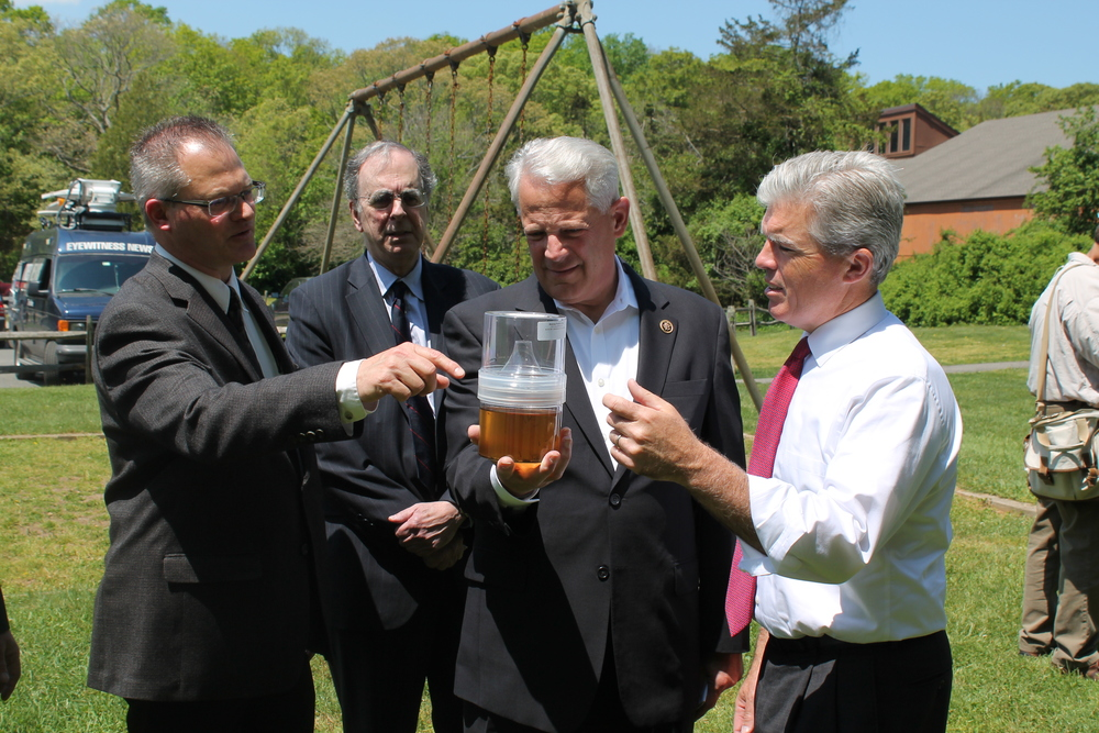 Rep. Steve Israel holds a container of mosquito larvae during a press conference Monday that saw state, county and town officials urge Congress for emergency funding to combat the Zika virus, which is spread by mosquitos. Israel, right-center, is pictured from left with Tom Iwanejko, chief environmental analyst for vector control at the Suffolk Department of Public Works; James Tomarken, M.D., Suffolk health commissioner; and Suffolk Executive Steve Bellone. Photo/Office of Rep. Steve Israel