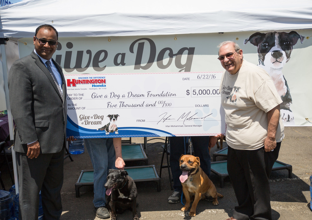 Huntington Supervisor Frank Petrone accepts a $5,000 check from Irfan Mohammed, general manager at Huntington Honda, on behalf of the town's Give A Dog A Dream Foundation.