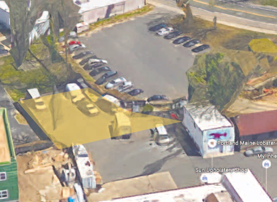 The public parking lot next to Huntington Elks Lodge, at top, is naturally elevated above a 7,000-square-foot paved parcel of land, roughly outlined in yellow, which the town has agreed to sell to the owner of 30 Stewart Ave., at bottom.  Photo/Google Maps