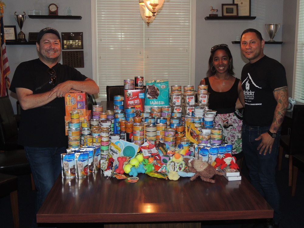 Little Shelter Executive Director David Ceely and Event and Operation Manager Tito Colon are pictured with Courtney Bynoe, associate executive director of the Huntington Township Chamber of Commerce. As part of the scavenger hunt, the Young Professionals donated over 400 cans of food and toys to the Little Shelter.