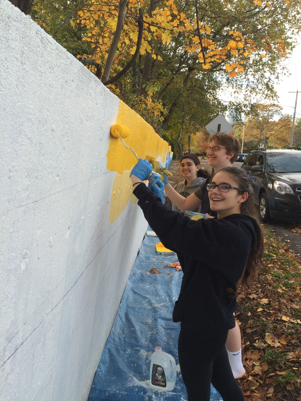Students of the Huntington High School Art Honor Society help paint the wall.